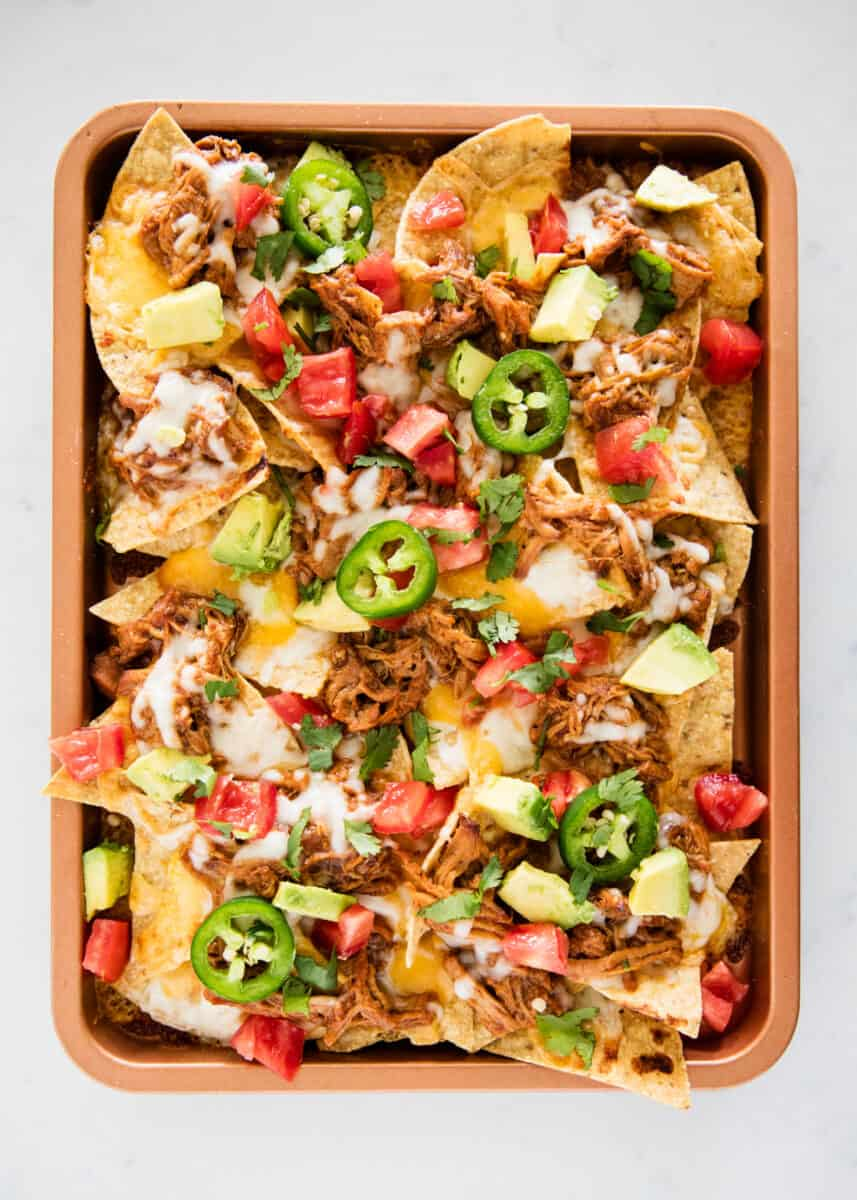 bbq pork nachos on sheet pan with toppings on top