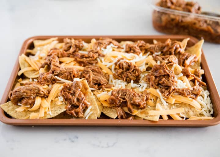 placing bbq pork on tortilla chips with cheese