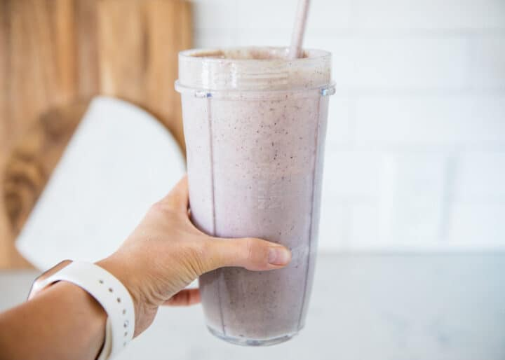 holding a berry protein smoothie