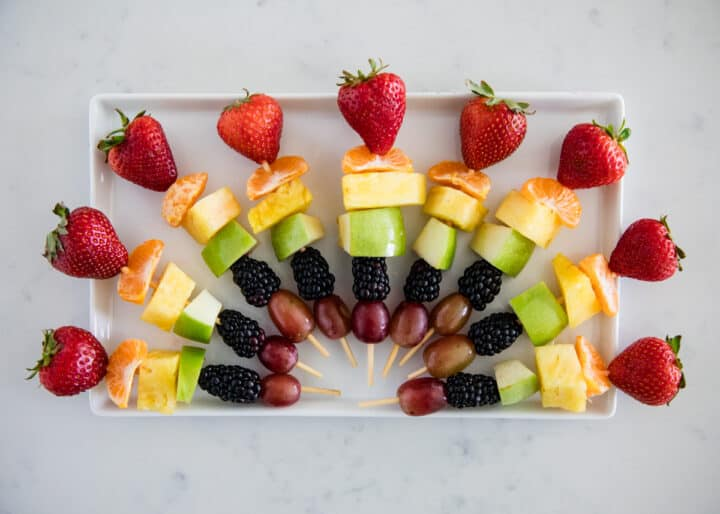 rainbow fruit kabobs on white plate