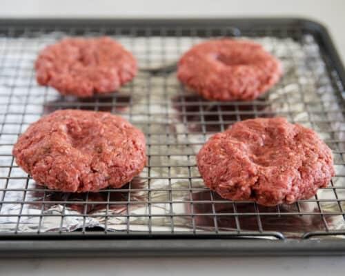 hamburger patties on baking sheet