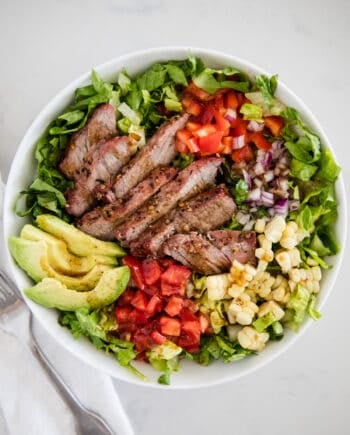 steak salad with avocado in white bowl