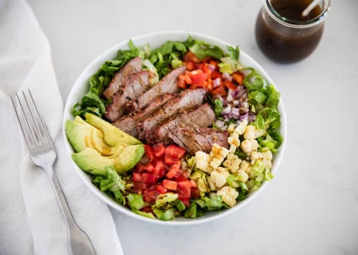 steak salad in a white bowl
