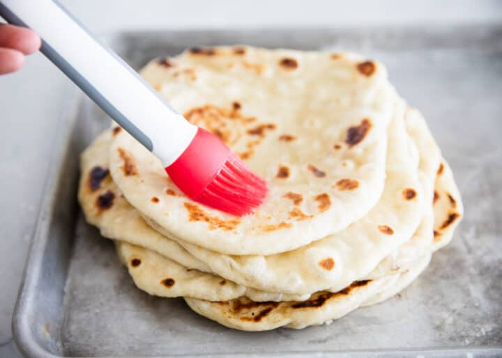 brushing butter on naan bread