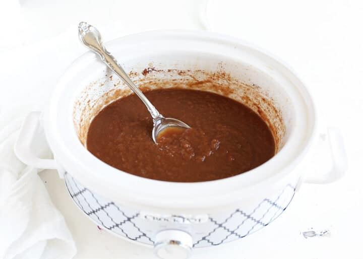 apple butter in crock pot with spoon