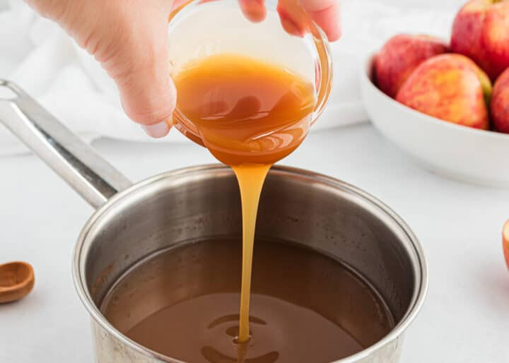 pouring caramel into pot of apple cider