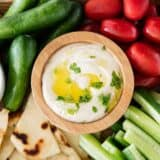 hummus in wooden bowl with vegetables