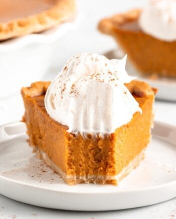 pumpkin pie with whipped cream on white plate with