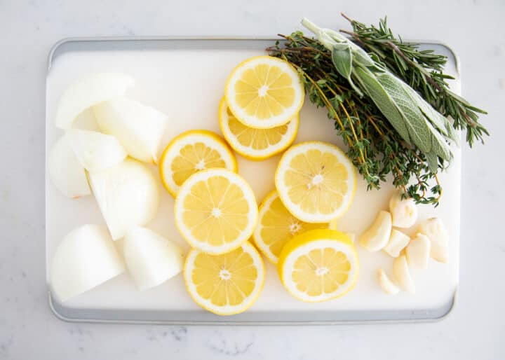 onions, lemons and herbs on cutting board
