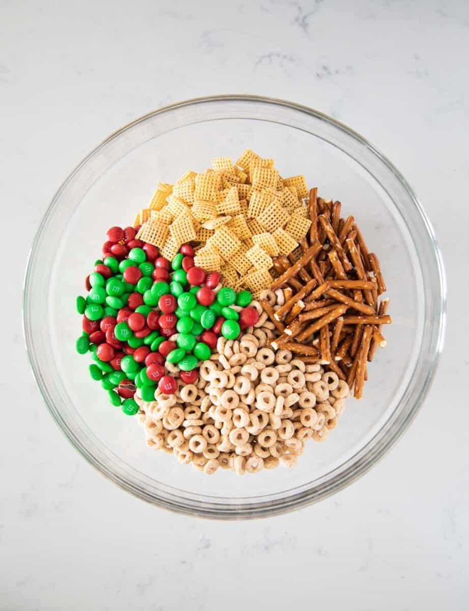 chex mix, pretzels, cheerios, and m&ms in bowl
