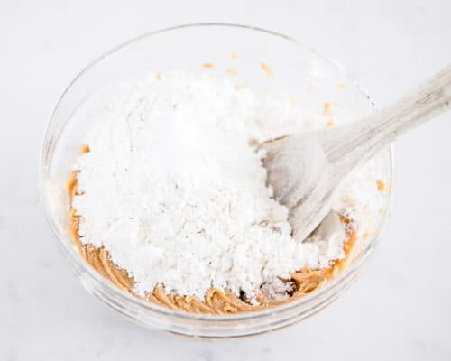 mixing peanut butter cookie dough with flour