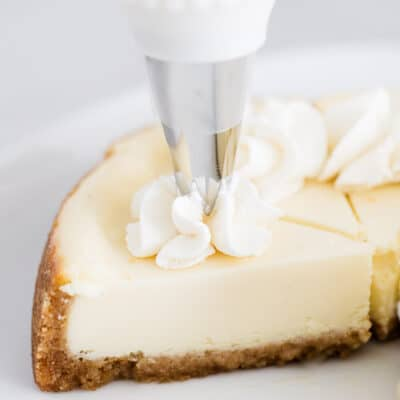 piping whipped cream on cheesecake