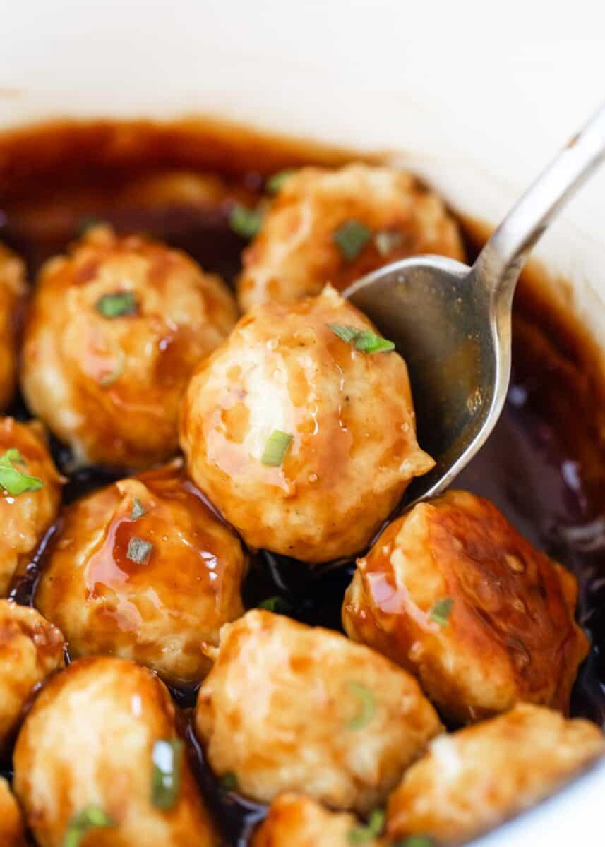 close up of teriyaki meatballs with spoon