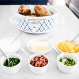 baked potato bar toppings in white bowls