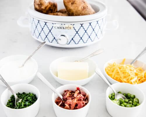 baked potato bar toppings in white bowls