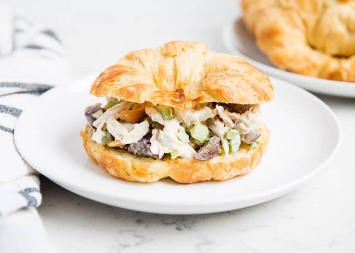 Chicken salad croissant on white plate