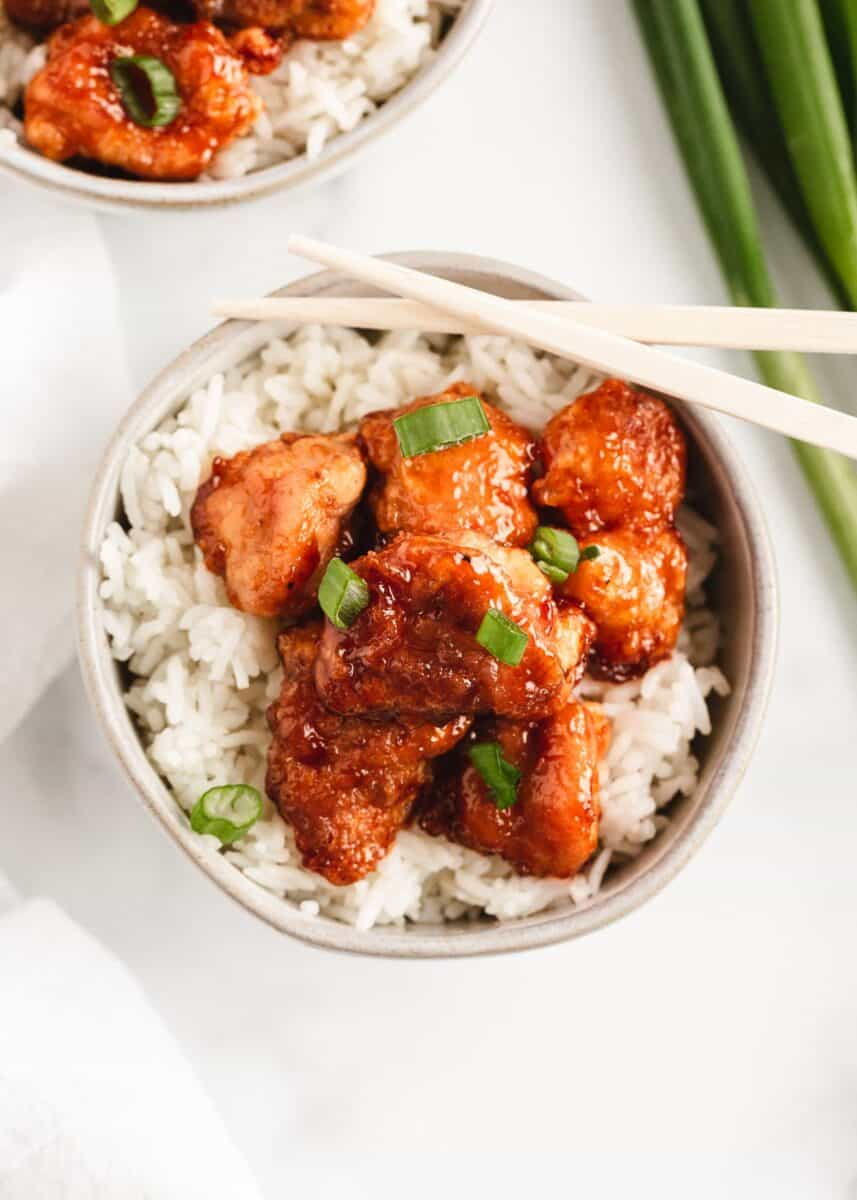 sweet and sour chicken and rice with chopsticks