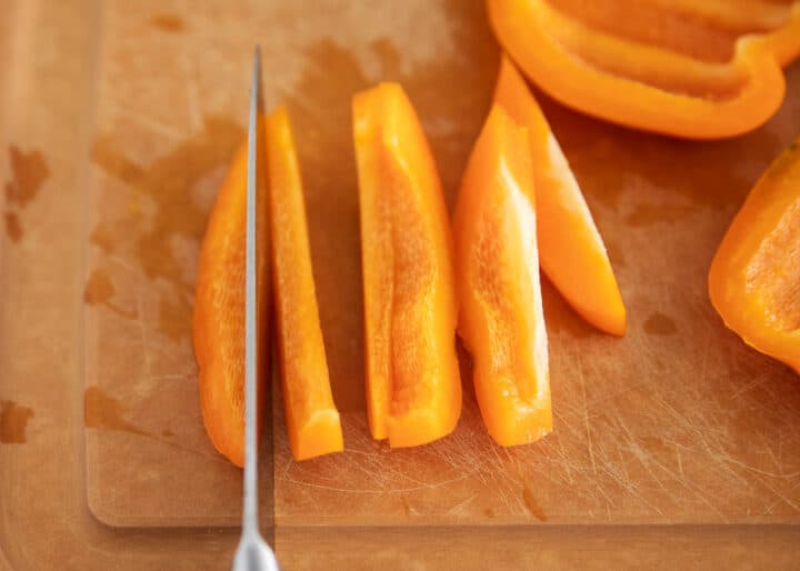 orange bell pepper being cut on cutting board