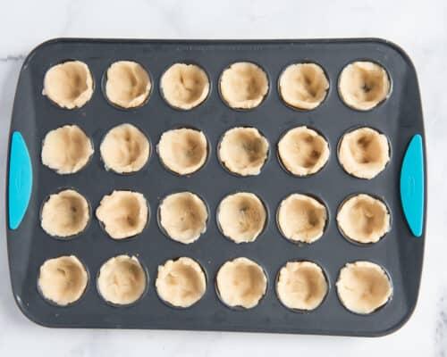 adding dough to mini muffin pan