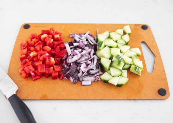 quinoa mediterranean salad ingredients on cutting board