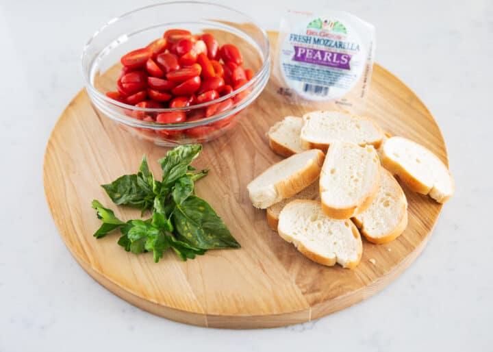 caprese bruschetta ingredients on wooden board