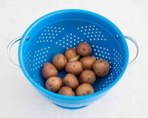 potatoes in blue draining bowl