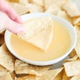 nacho cheese dip and chips on table