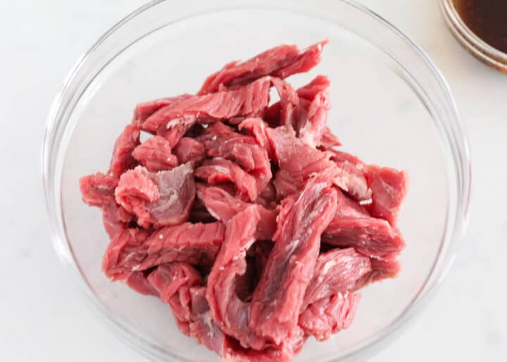 teriyaki raw steak slices in clear bowl