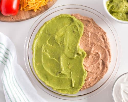 spreading guacamole onto bean dip