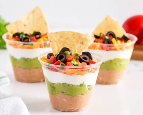 7 layer dip in plastic cups with tortilla chips