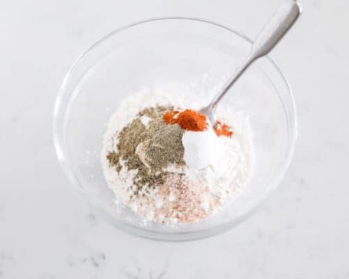 mixing flour and seasonings in bowl