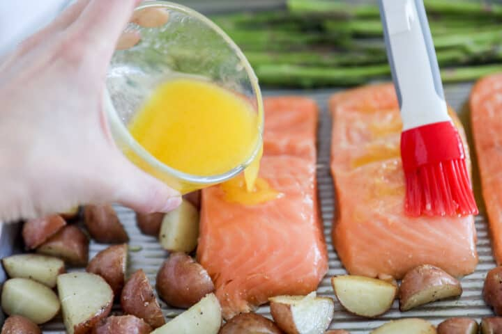 pouring butter sauce over salmon