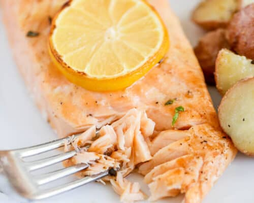 fork with salmon on white plate
