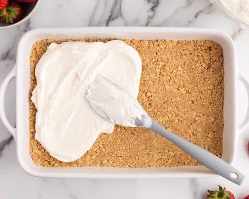 spreading cream cheese over graham cracker in pan