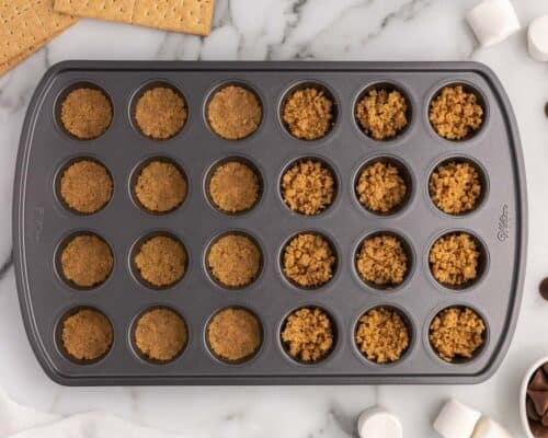 pressing graham crackers into muffin pan