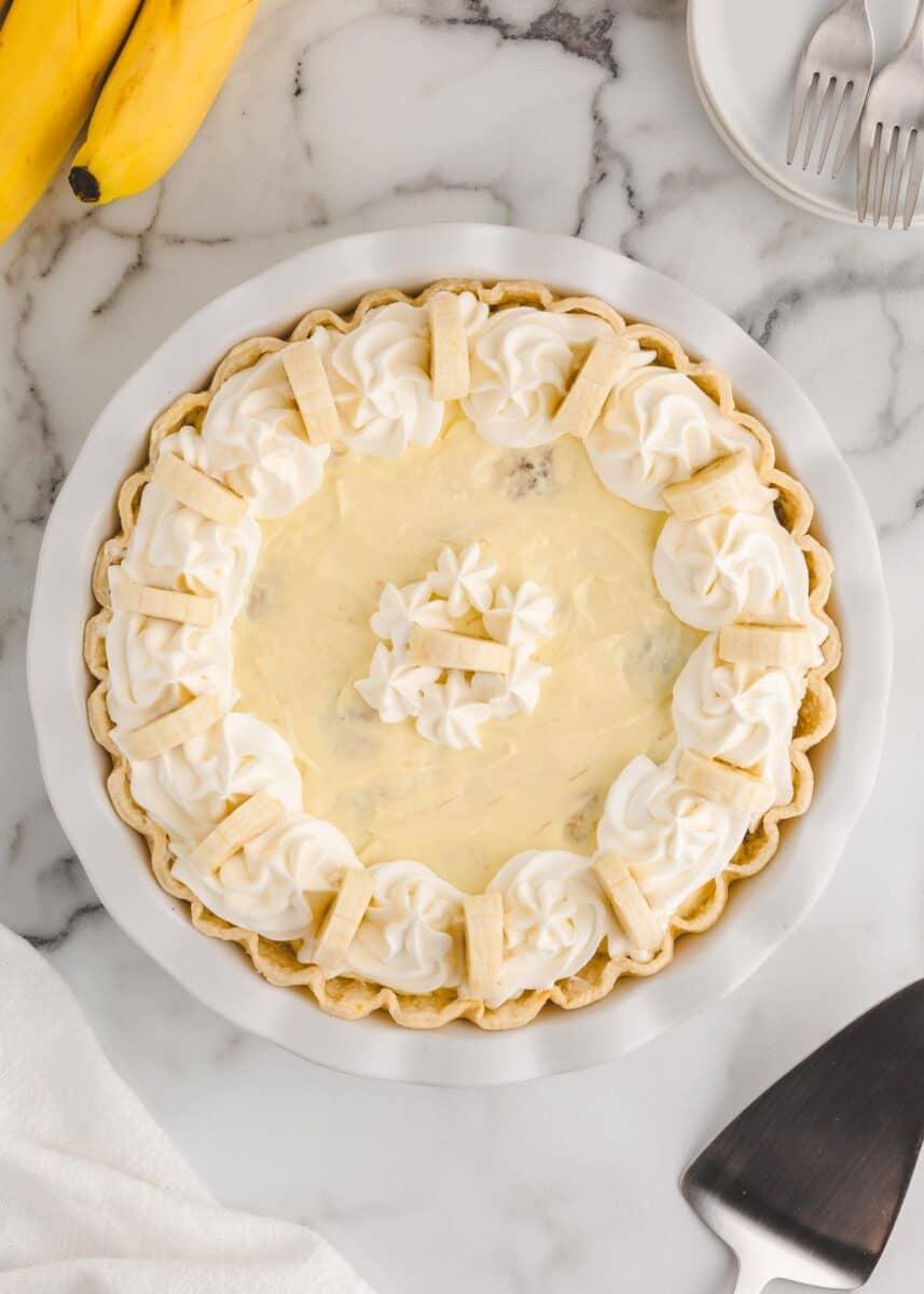 banana cream pie in white pie tin