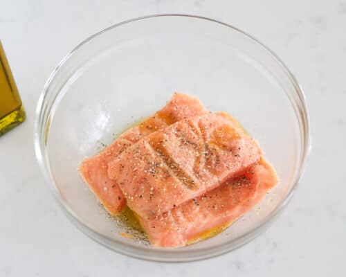 salmon and olive oil and seasonings in bowl