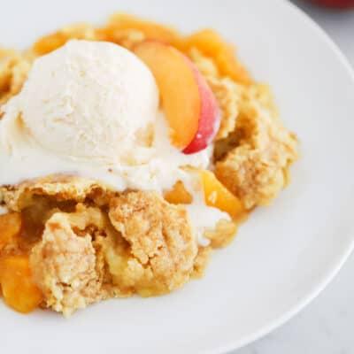 peach dump cake and ice cream on white plate