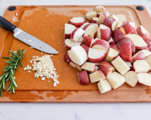 sliced potatoes and rosemary on cutting board