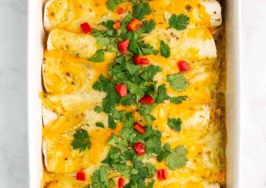 green chile chicken enchiladas in casserole dish