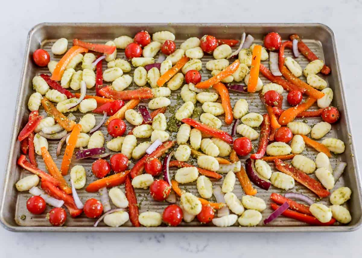 gnocchi and vegetables with pesto on pan