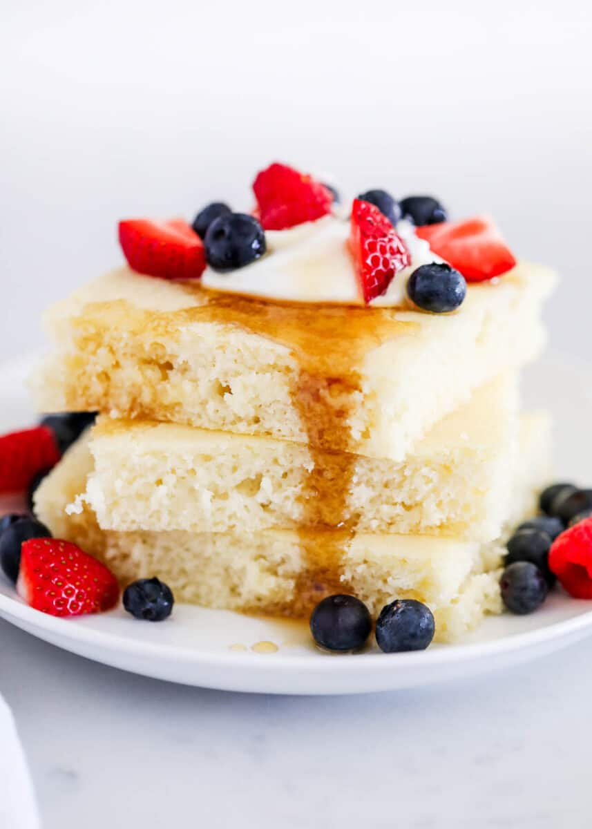 stack of sheet pan pancakes with syrup and berries
