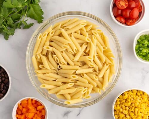 pasta in bowl with salad ingredients