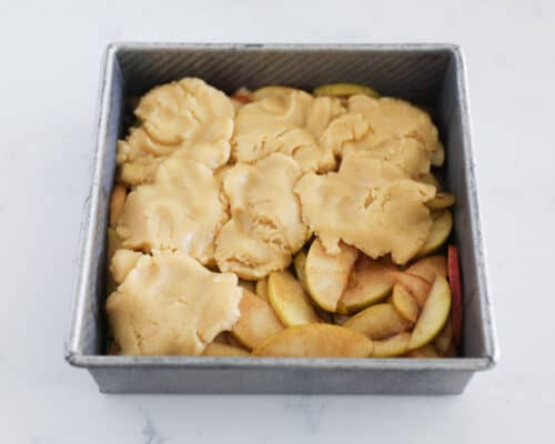 dough on top of apples in pan