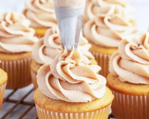 piping cinnamon buttercream onto cupcakes