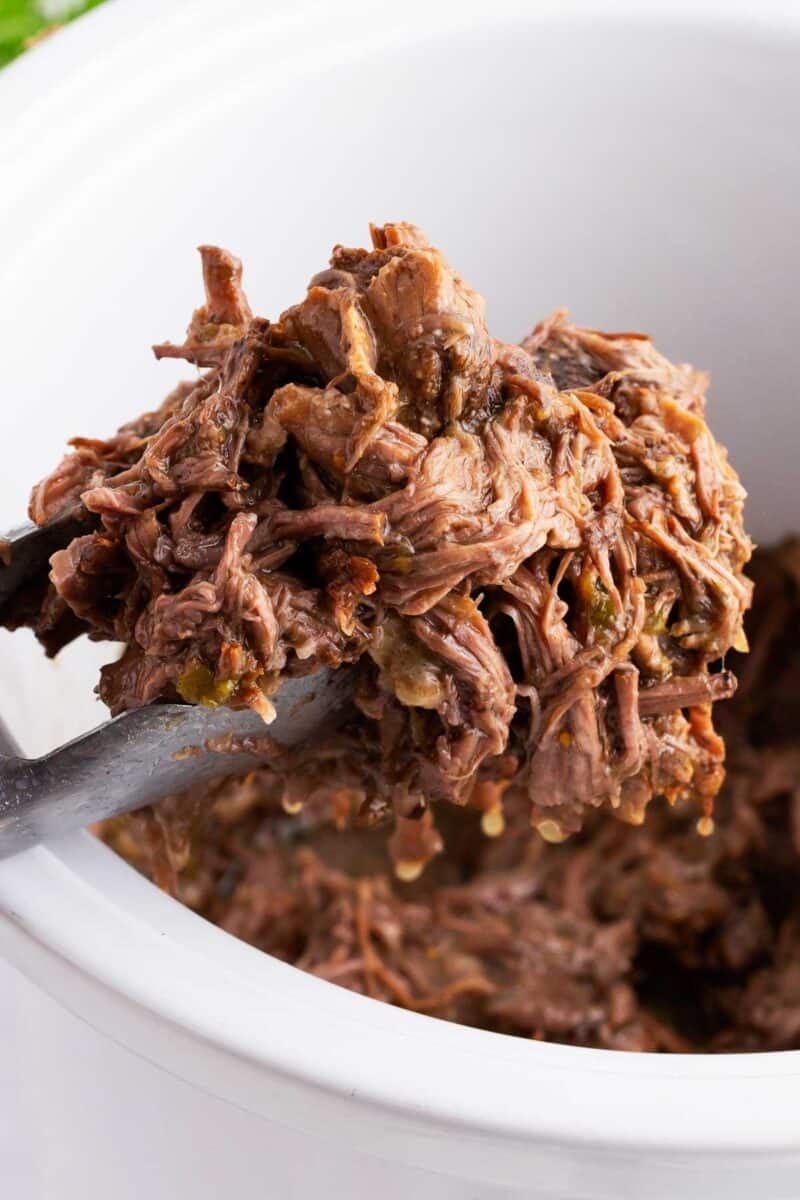 tongs holding up shredded beef