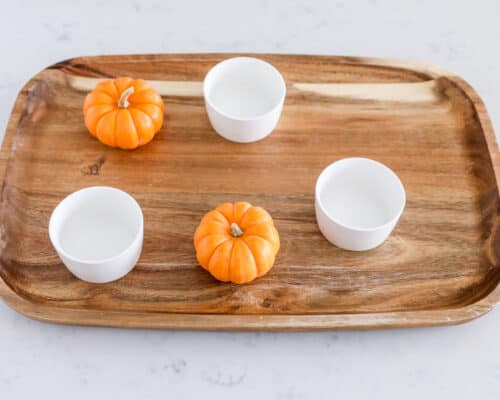 board with bowls and pumpkins on top