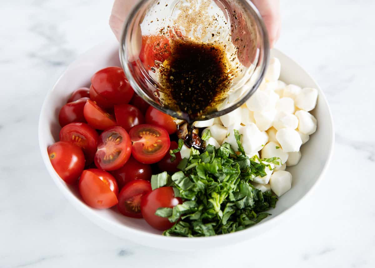 pouring dressing over caprese salad