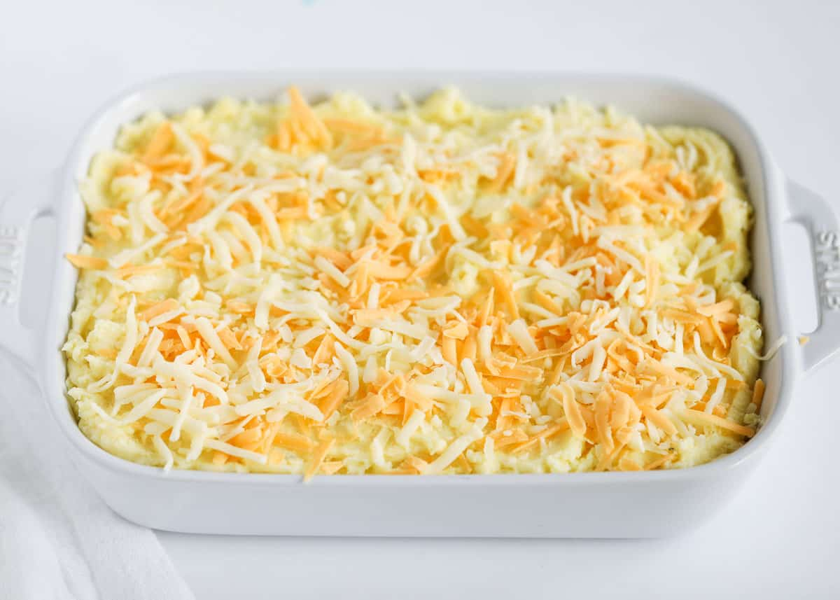 cheese on top of potatoes in baking dish