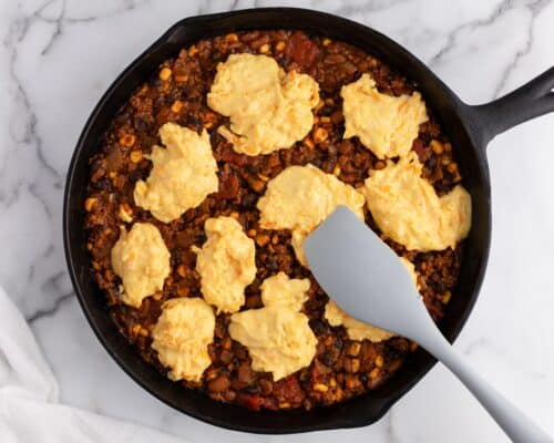chili skillet with spoonfuls of cornbread on counter